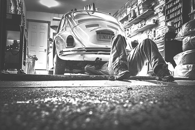 Un homme bricole sous sa voiture